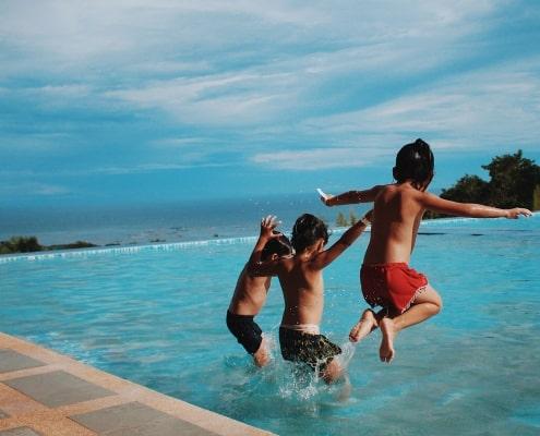 Drie jongens die in het water springen   Groen Rechts